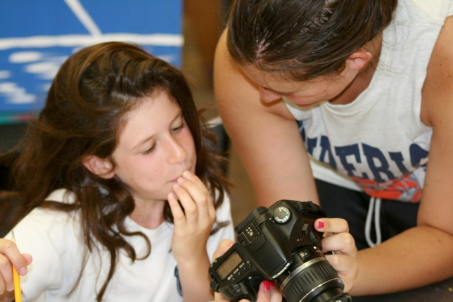 Counselor teaching a camper how to use a camera