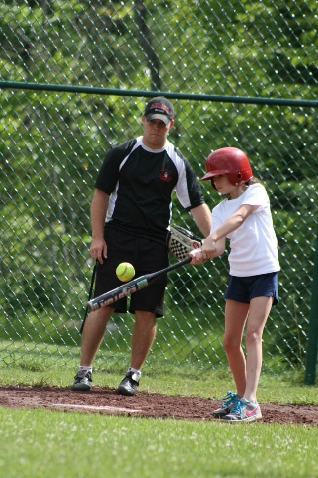 A camper swings at a softball under the watchful eye of a coach