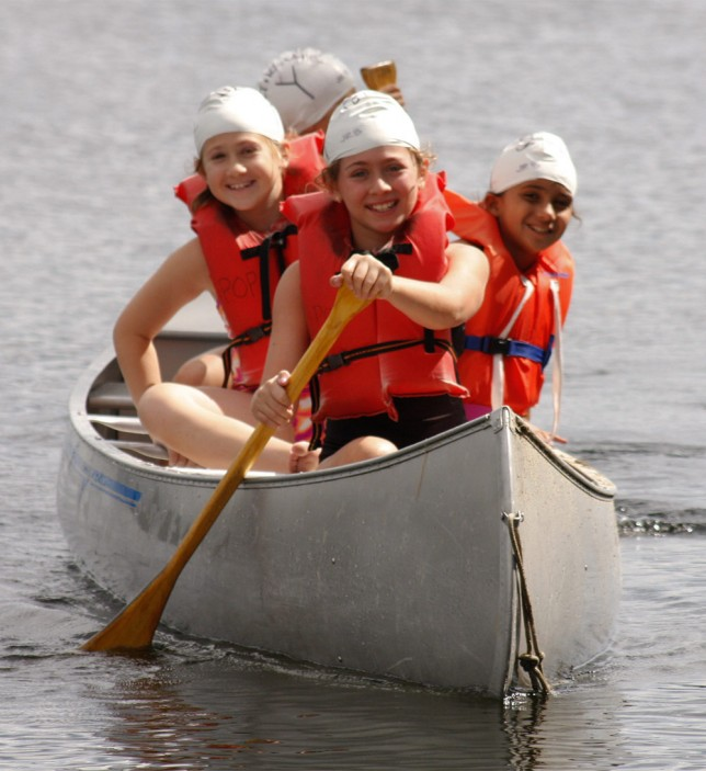 Campers rowing towards the camera in a canoe