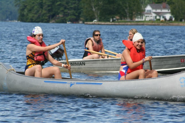 Campers and counselors on the lake in canoe and boat