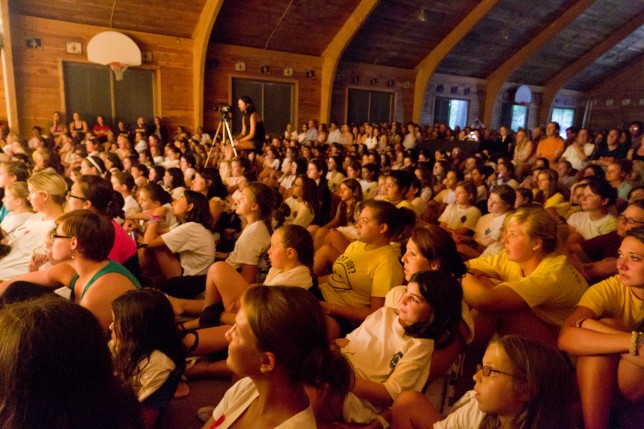 Parents, campers, and counselors sit enthralled in the audience
