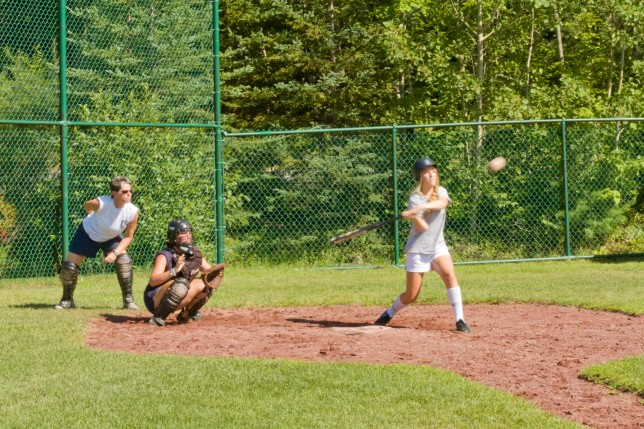 A batter swinging at the softball