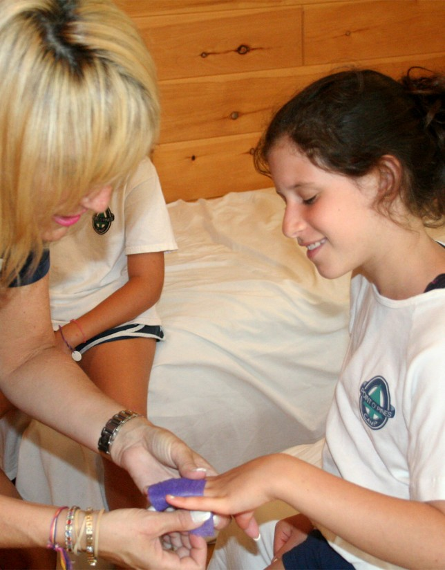 A registered nurse gently wraps a camper's fingers