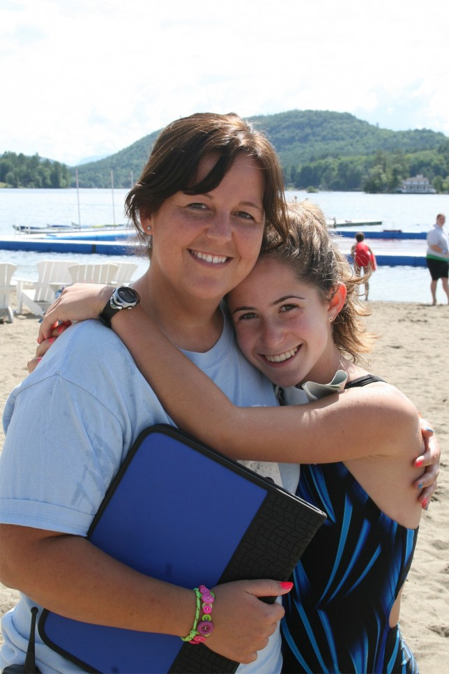 A counselor and camper hugging on the waterfront