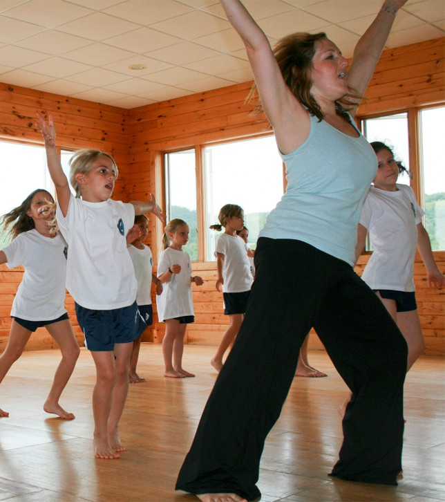 A dance instructor leading younger campers