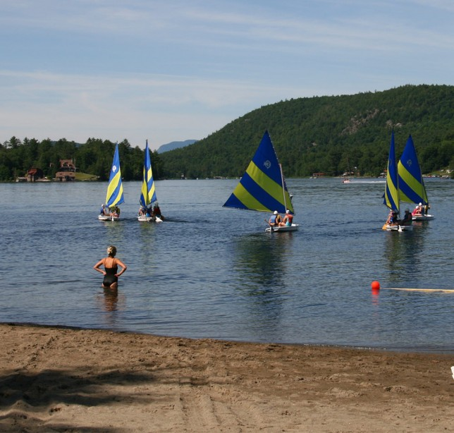 A counselor supervising campers sailing on Brant Lake