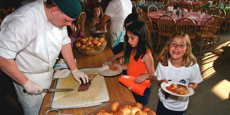 Campers being served by a camp chef