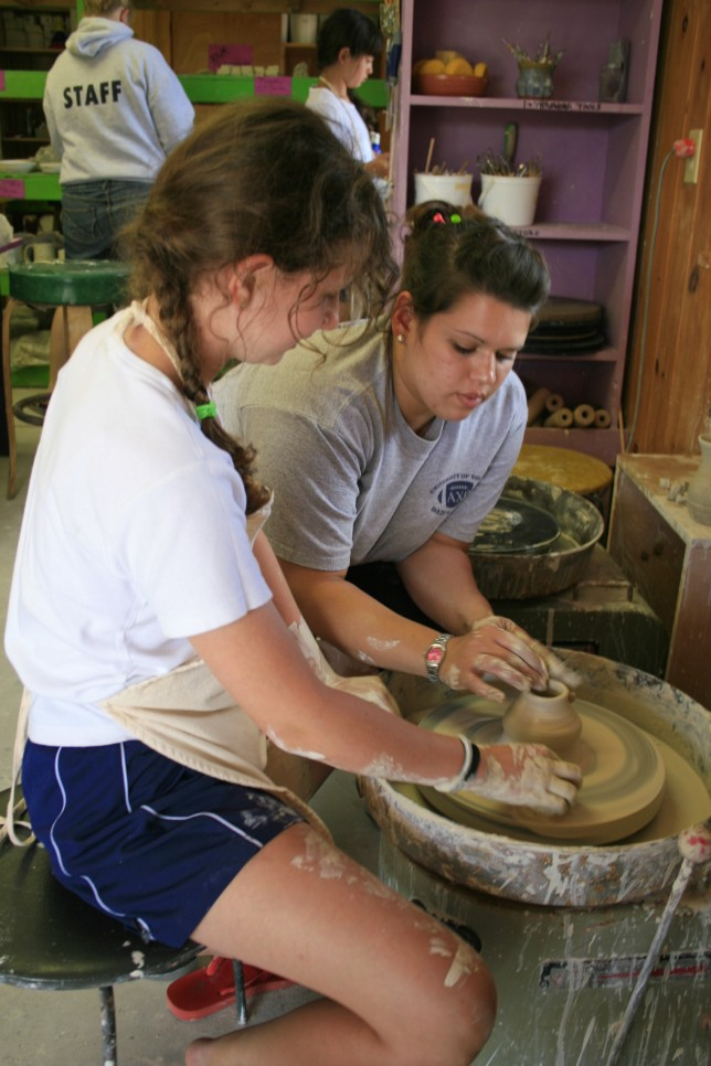 A counselor teaches a camper to spin a mug on the pottery wheel