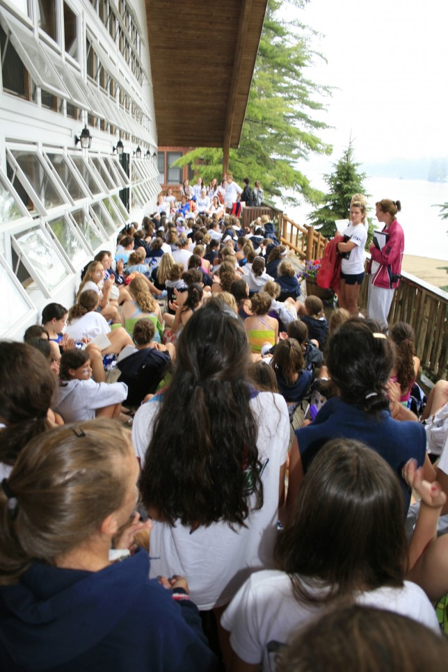Campers listen to announcements on the front porch of the dining hall