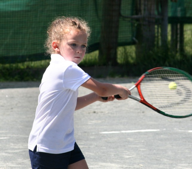 Little girl returning a tennis serve
