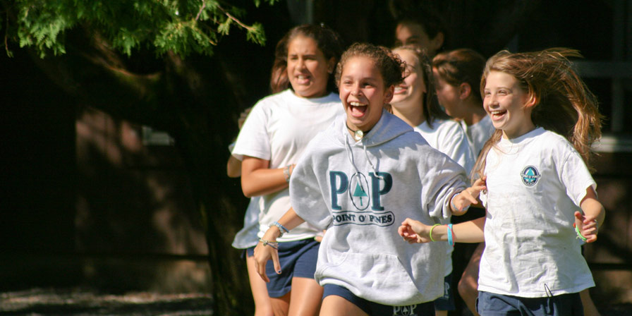 A group of campers running to the next exciting activity at Point O'Pines.
