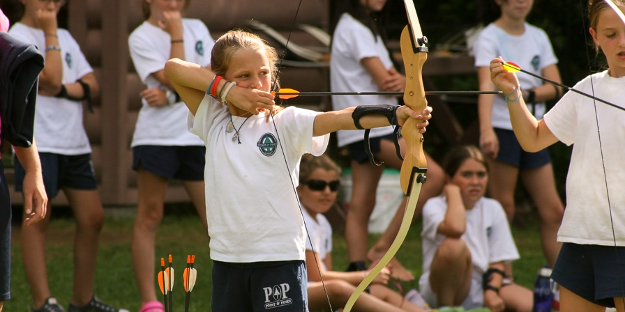 Camper aims at Archery while friends watch