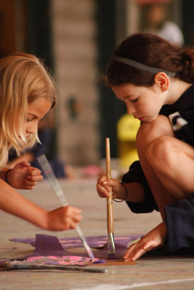A pair of campers painting together in our Arts and Crafts program