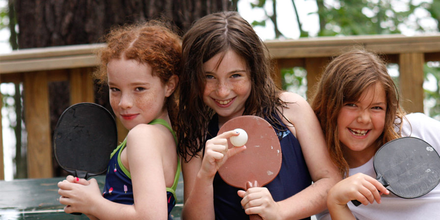 Campers with their ping-pong paddles and a ball.