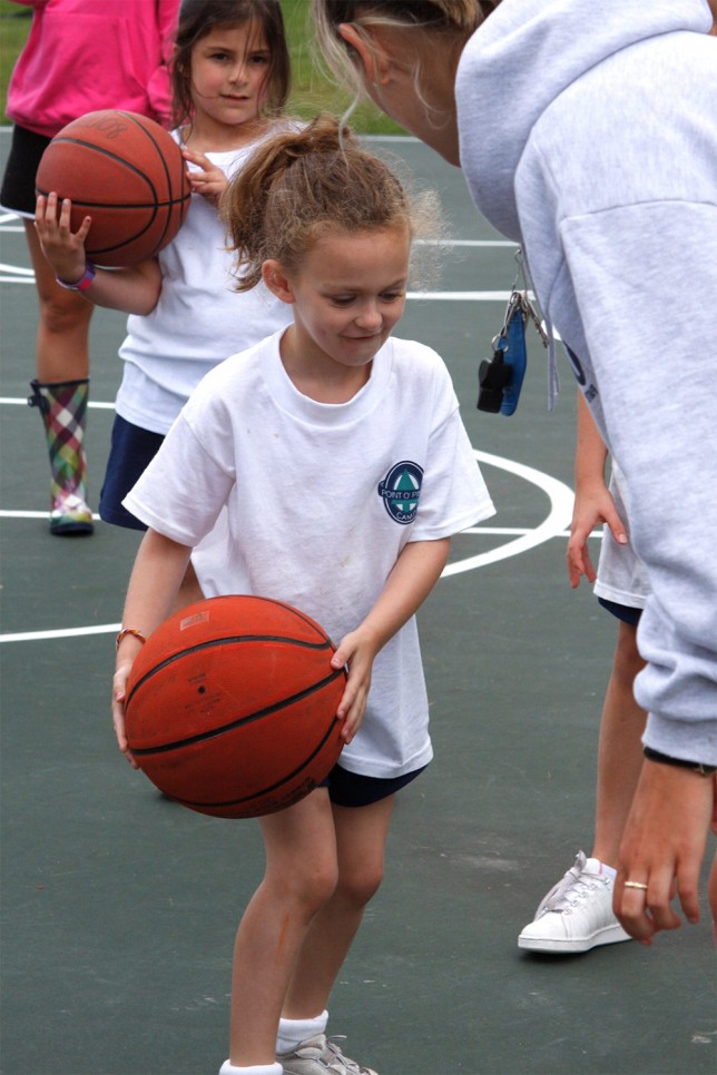A basketball instructor teaches a young player to dribble