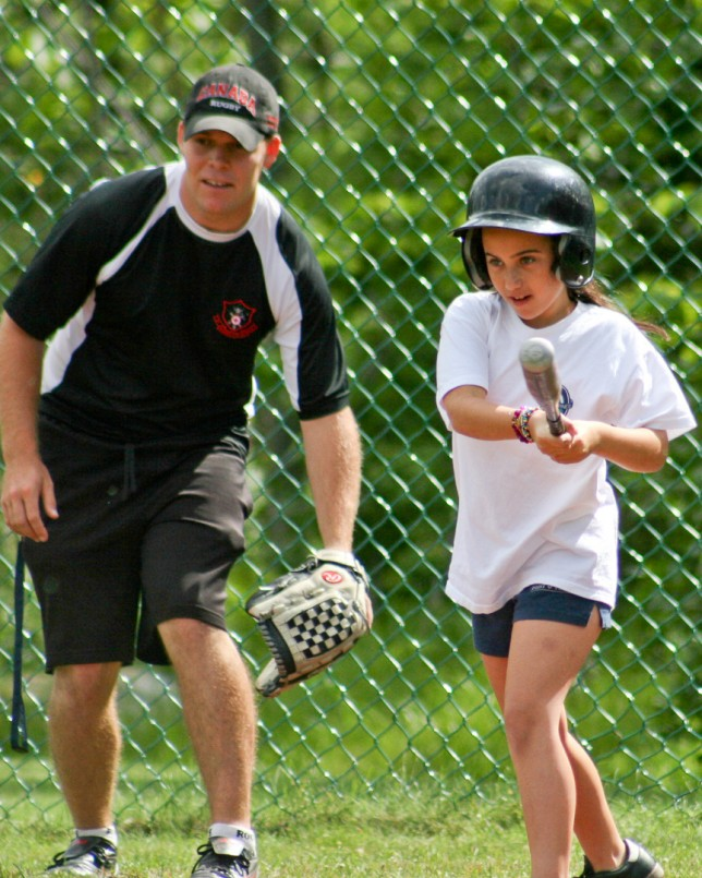 A softball instructor watches a camper's swing