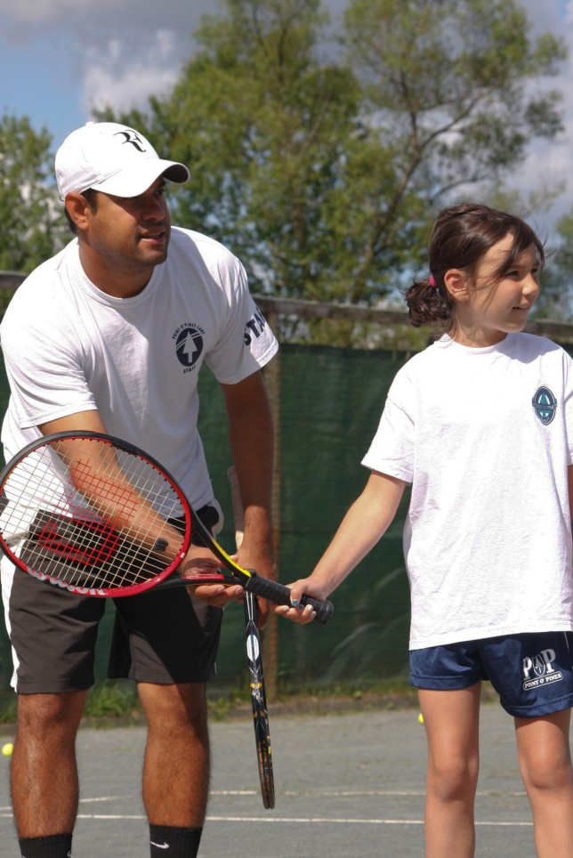 Lead tennis instructor helping a camper with her swing
