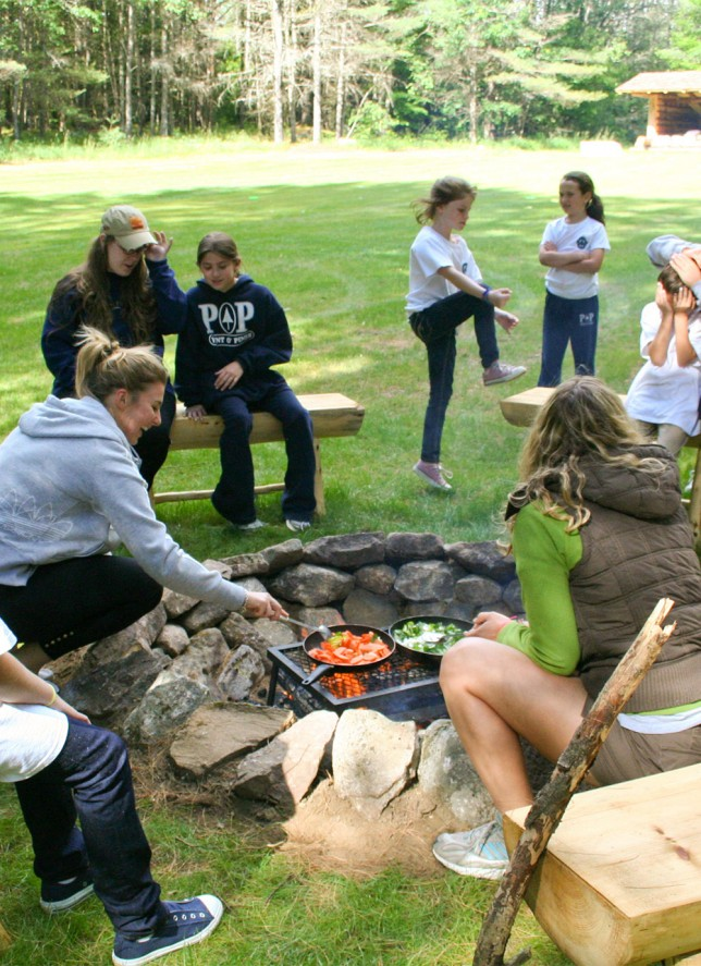 Counselors preparing breakfast over a fire for sleepy campers