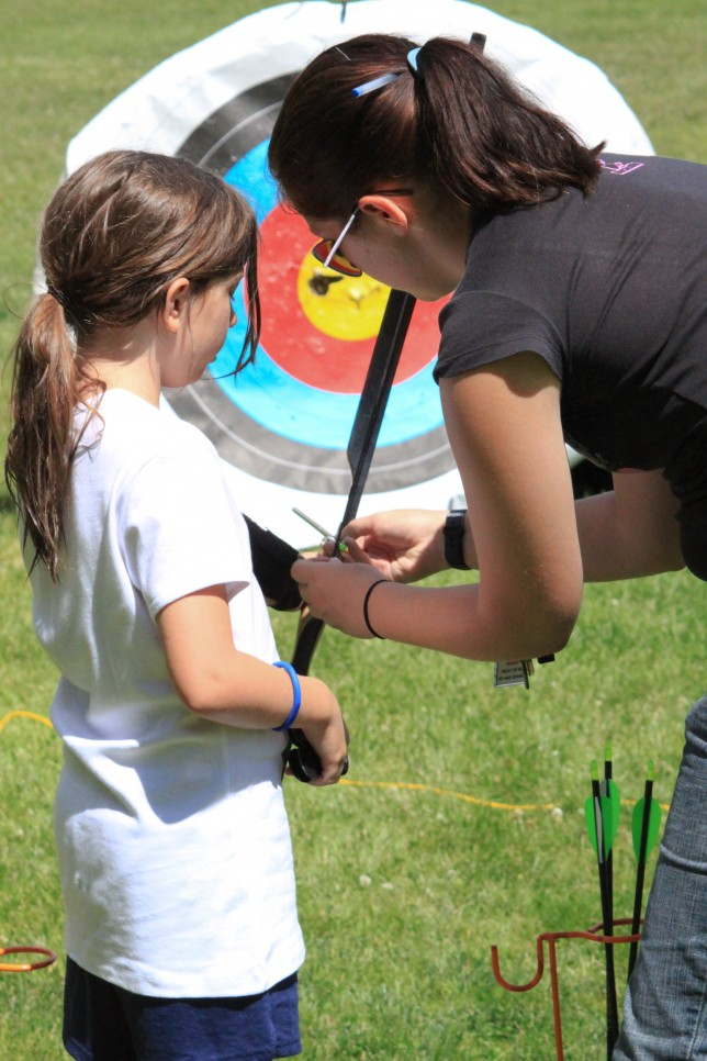 An archery counselor teaches a camper to shoot a bow