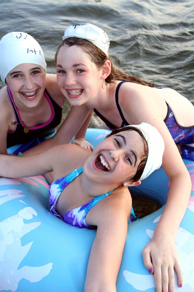 Three campers having fun in an inner tube