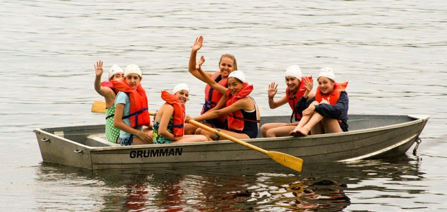 A counselor waving from a boat full of campers