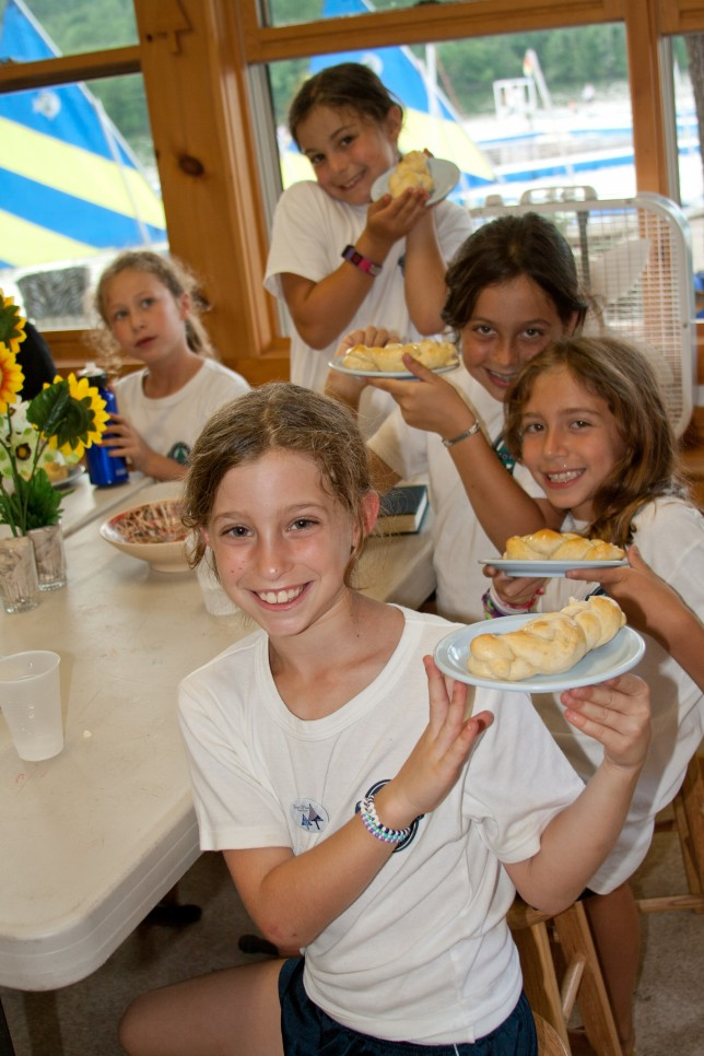 Campers showing off the braided bread they've made in cooking