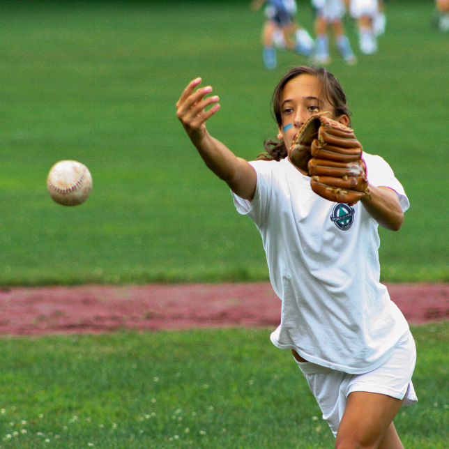 A young camper pitching a softball