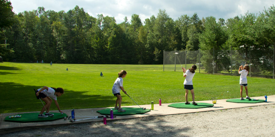 Campers practicing their swing at the driving course.