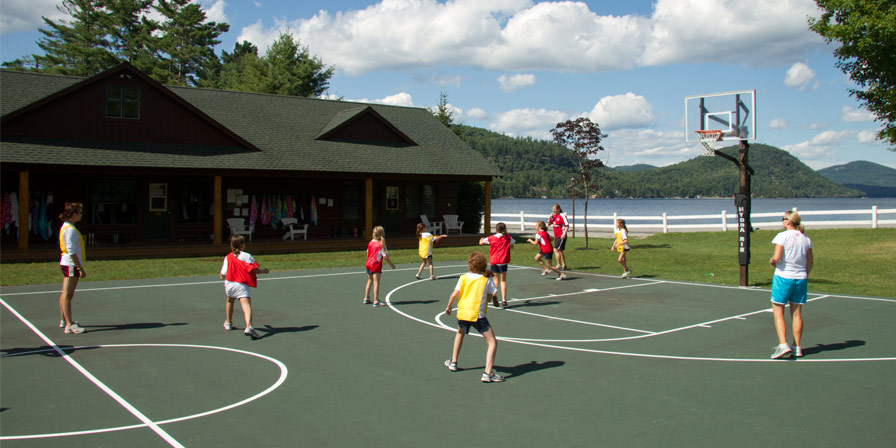 Two teams of campers play a game of basketball.