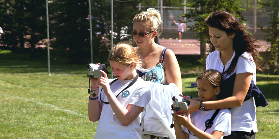 Staff teaching campers how to use camcorders