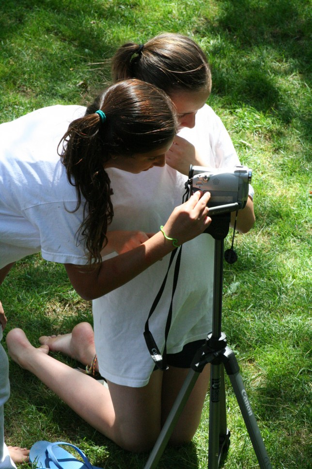 Two campers getting the right shot with a camcorder