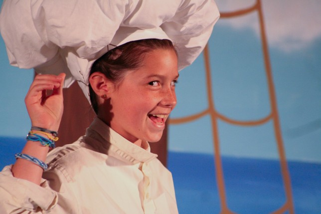 A young girl playing a chef