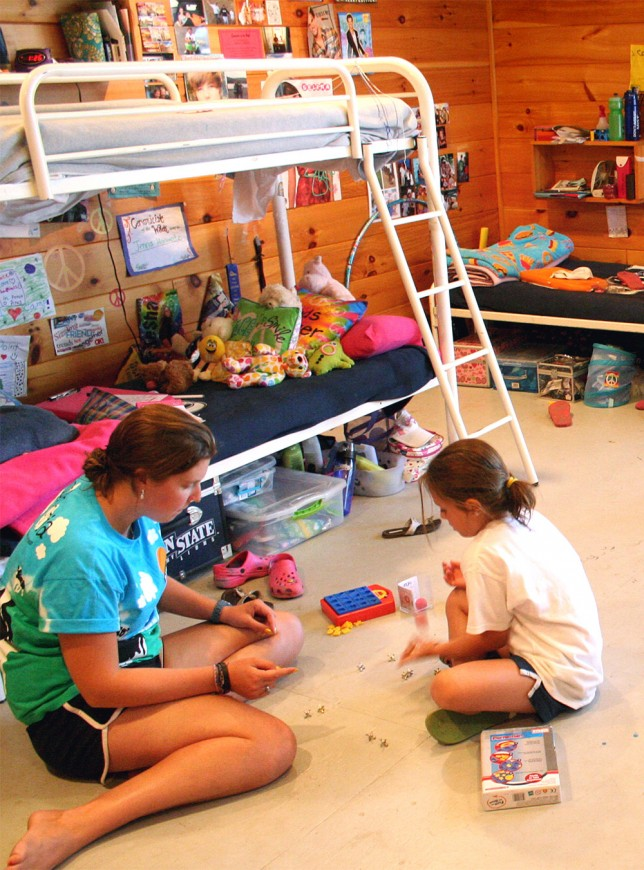 A counselor and camper playing jacks on the floor of their cabin