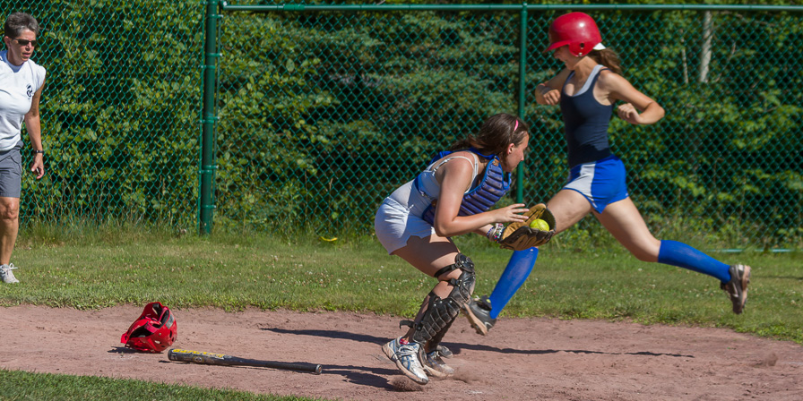 Catcher trying to stop the runner at home plate.