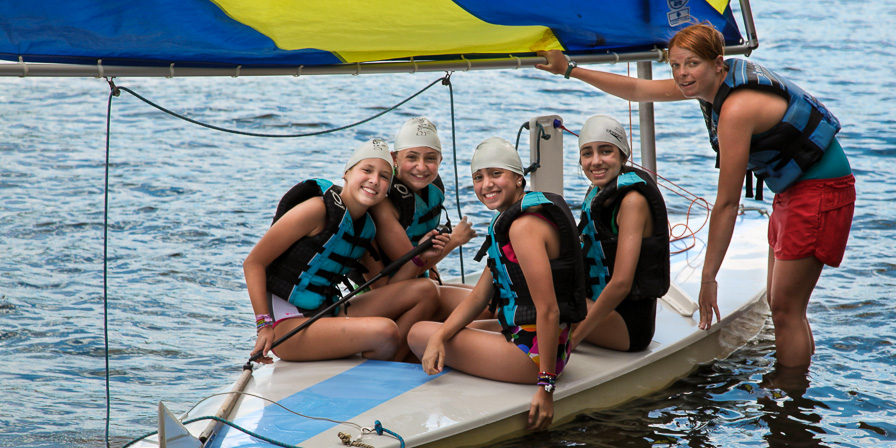 Campers set sail with some help from their counselor.
