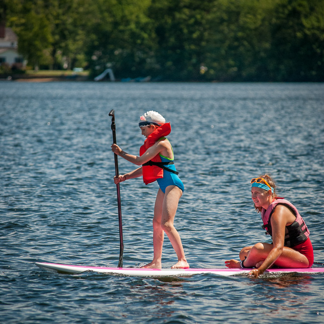 Camper learns stand-up paddle board.