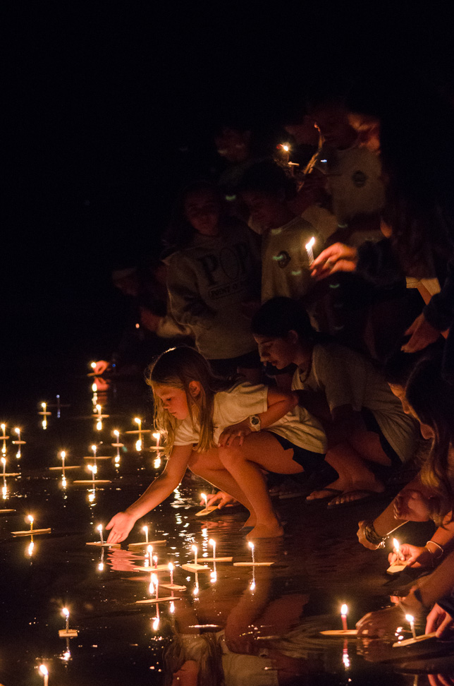 Campers light candles on wish boats