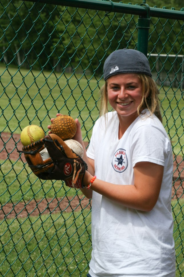 A counselor carrying balls in her softball mit