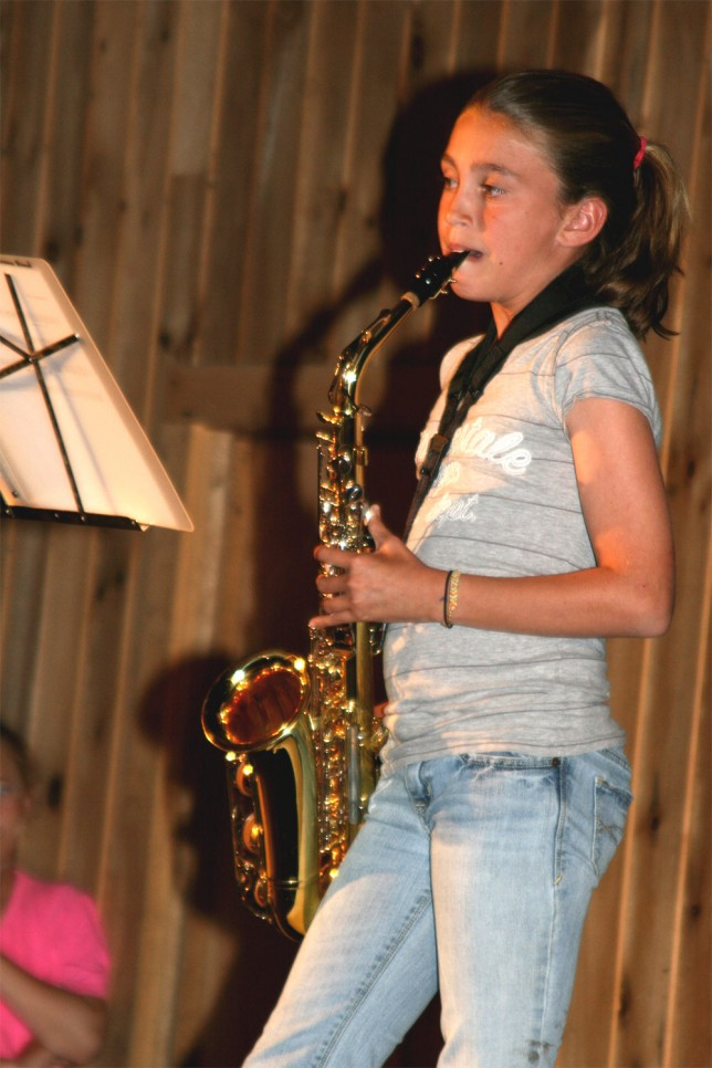 A young camper playing the saxophone