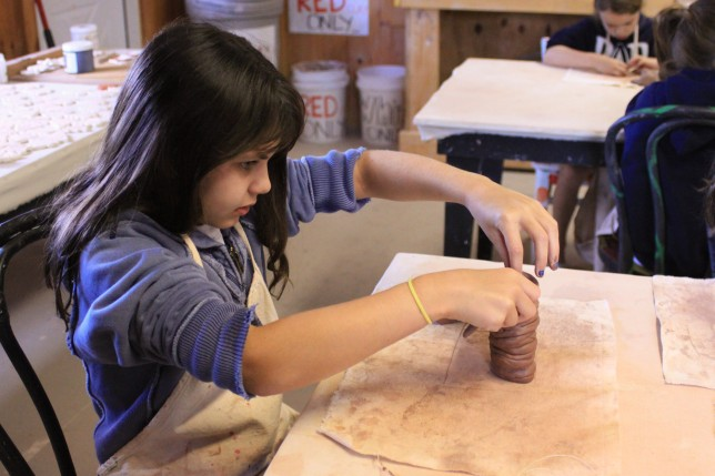 A camper making a pot in the ceramics building