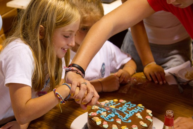 A counselor helps a camper cut her birthday cake