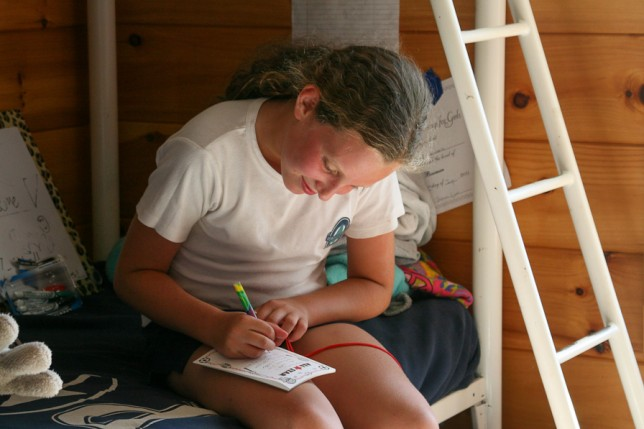A camper sitting on her bunk writing a letter