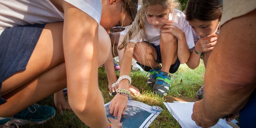 Campers learning map and compass skills for directions for their outdoor adventures.
