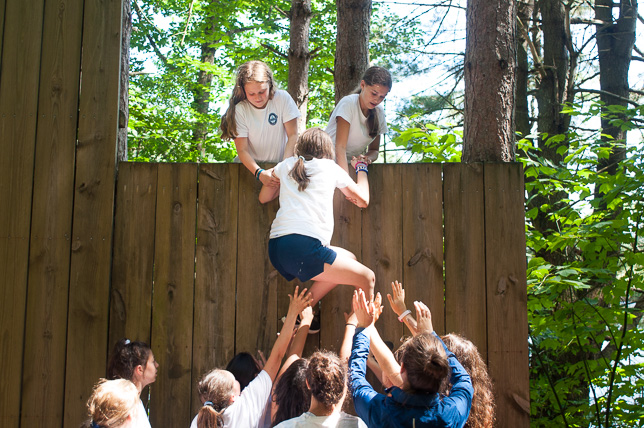 Campers cooperating to conquer the wall at the POP Farm