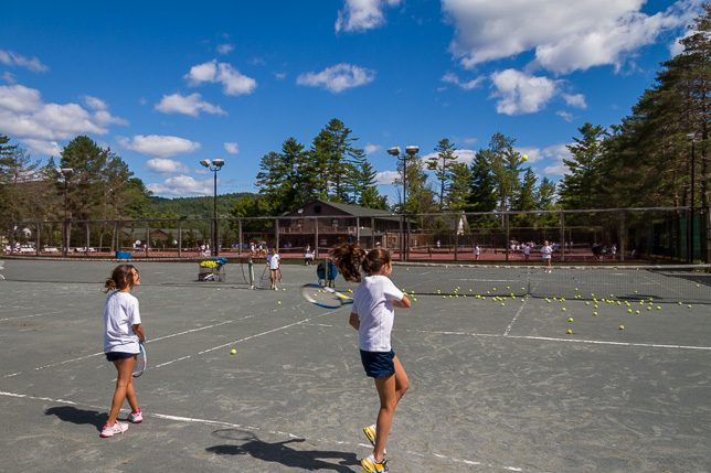 Campers practice hitting on green Har-Tru courts.