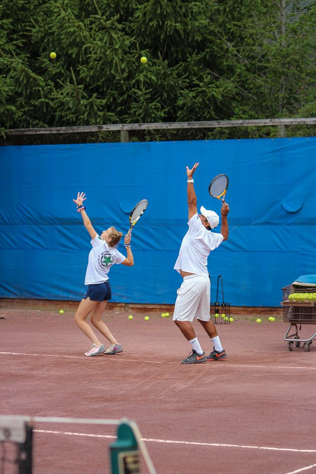 Tennis instructor and camper show proper tennis serve motion to campers.
