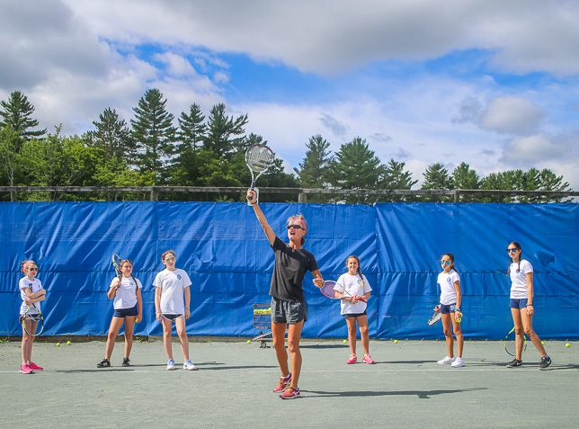 Tennis instructor shows serving form to campers.