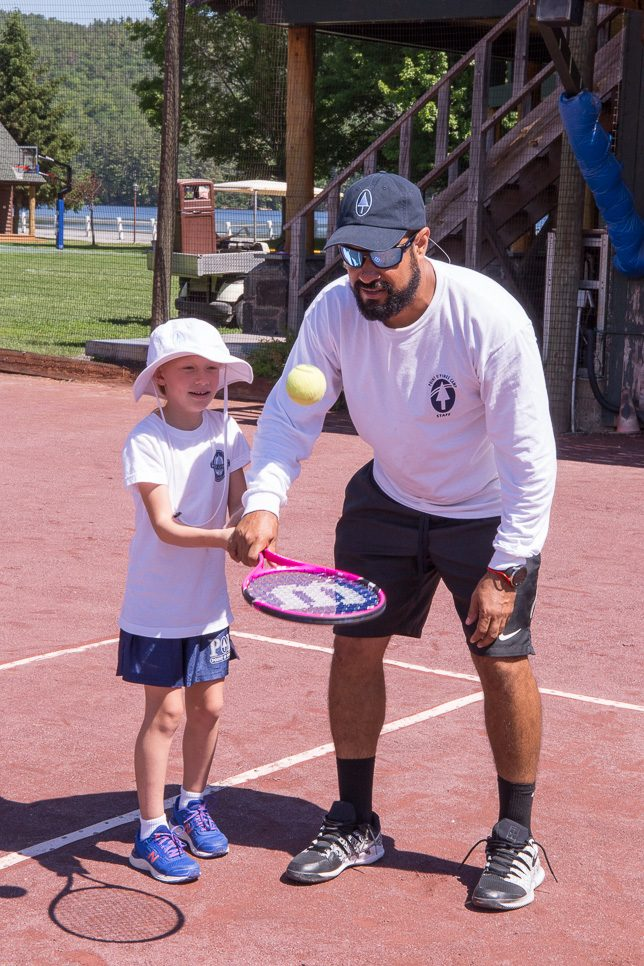 Tennis coach shows young player how to bounce the ball on her racquet