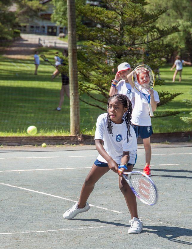 Young campers practicing their tennis.