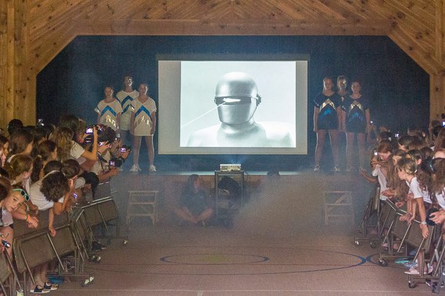 Peak leaders flank a Robot on the screen in a smoky Rec Hall.